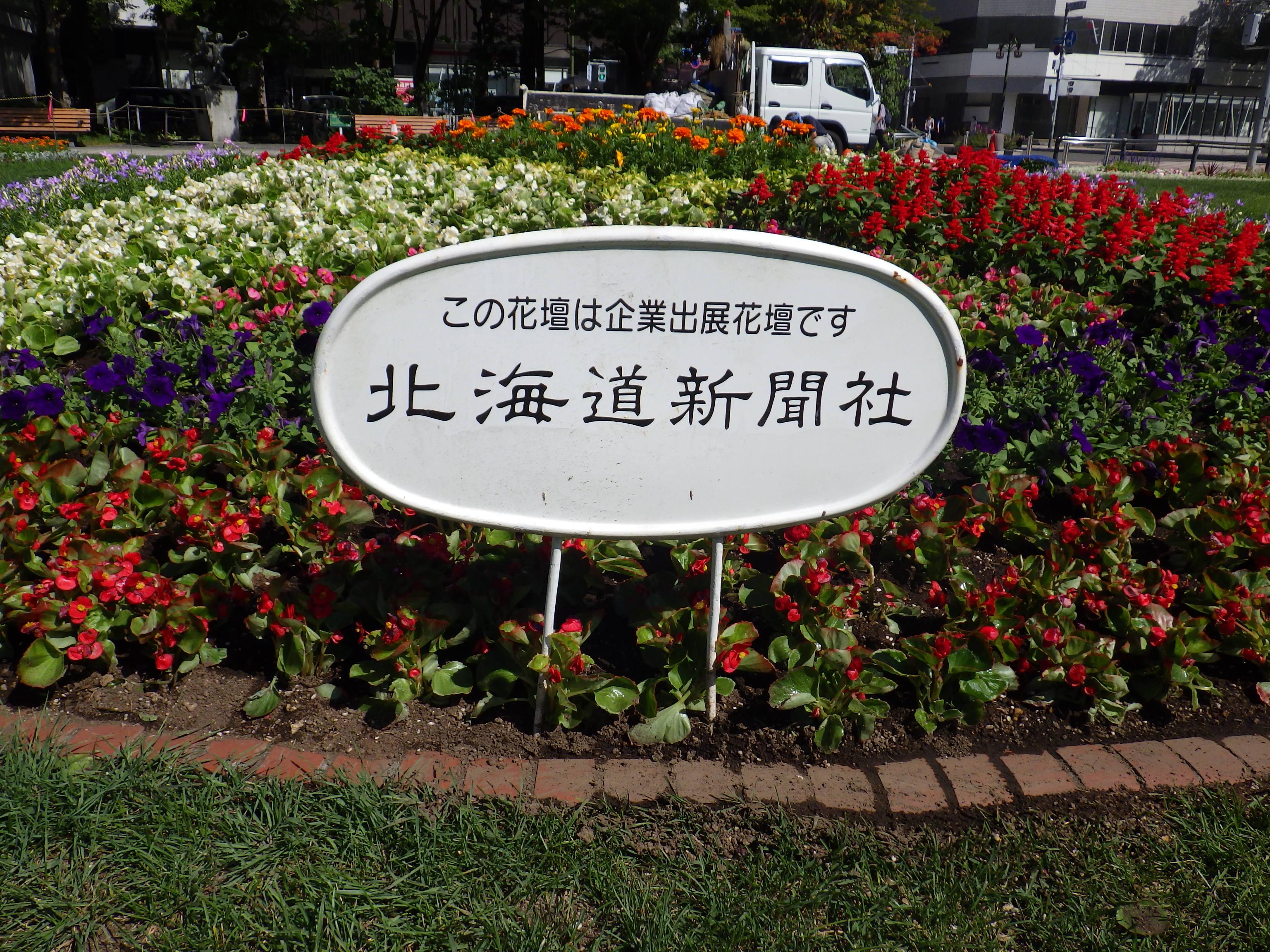 西3丁目東側の北海道新聞のスポンサー花壇の看板