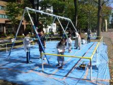 10月6日の遊具塗装体験で4人用ブランコに塗装をする子どもたち