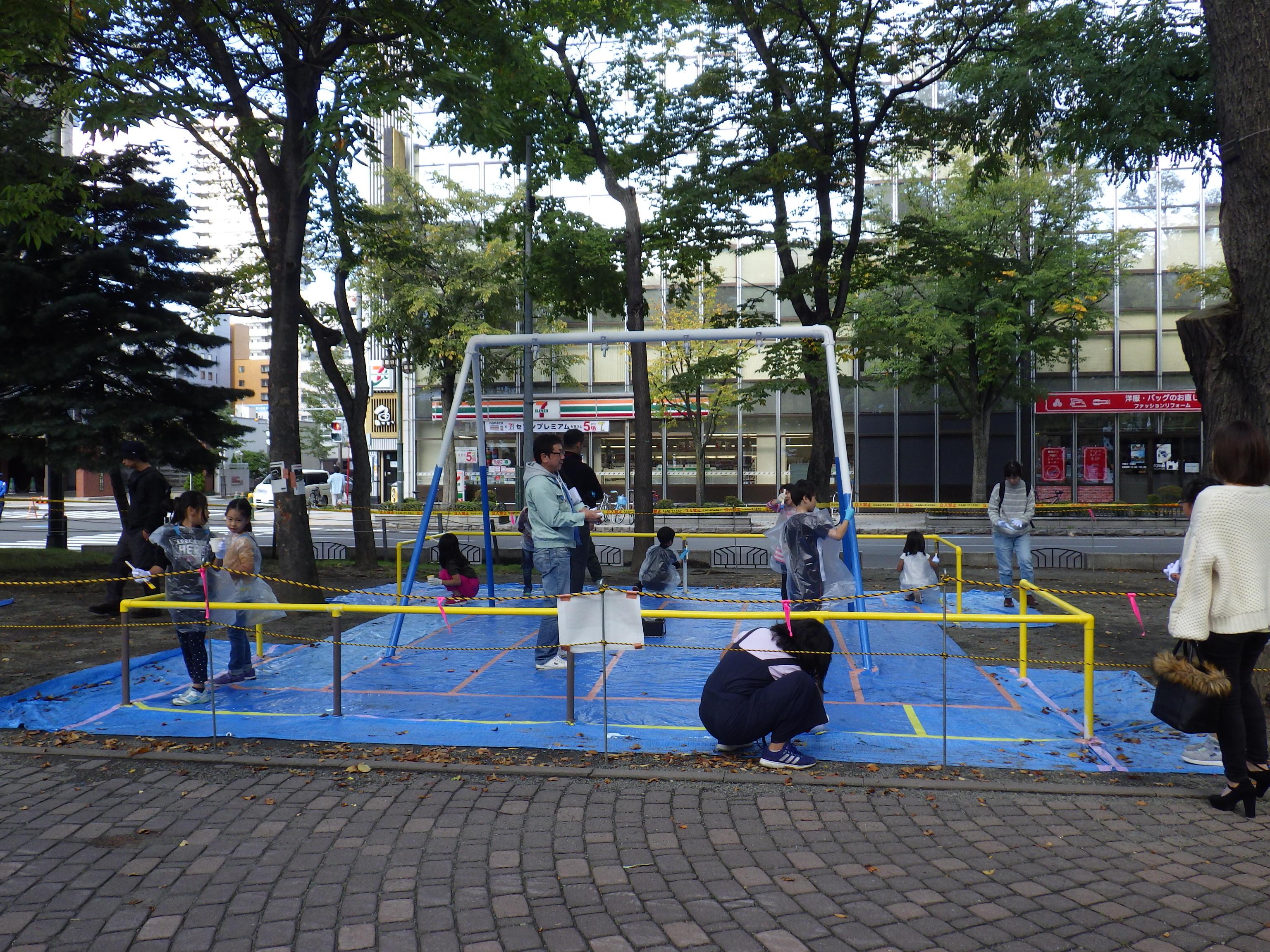 10月6日の遊具塗装体験で2人用ブランコに塗装をする子どもたち